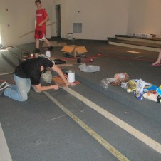 5/26/12 Brannon gluing carpet on the stage. Billy & Sarah Reynolds came to help bring lunch.