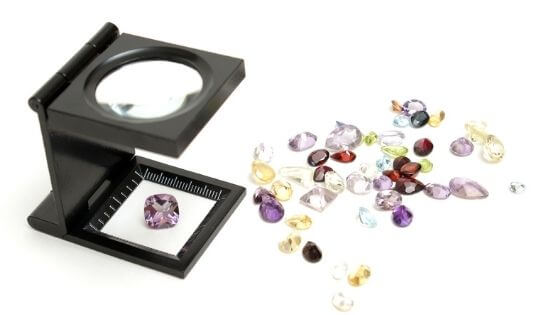 Inspecting gemstones to see if they're real or fake.