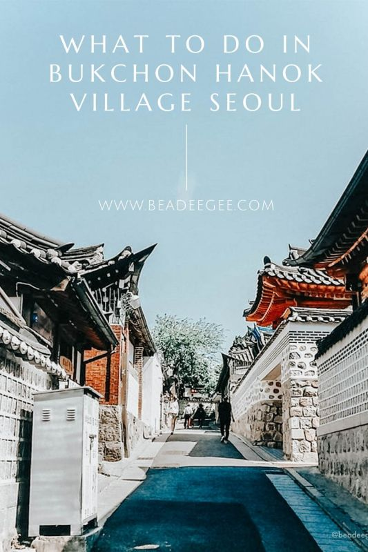 An empty alleyway of hanoks with text What to do in Bukchon Hanok Village Seoul