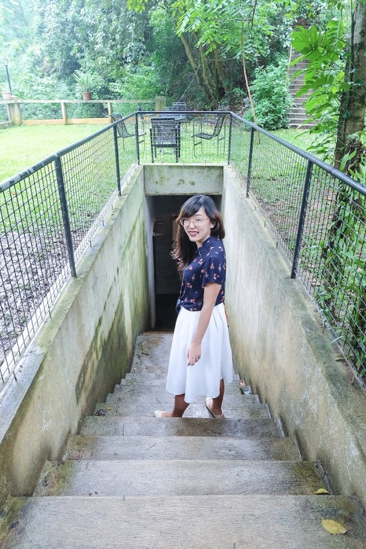 a girl on a cemented stair leading to the underground cafe