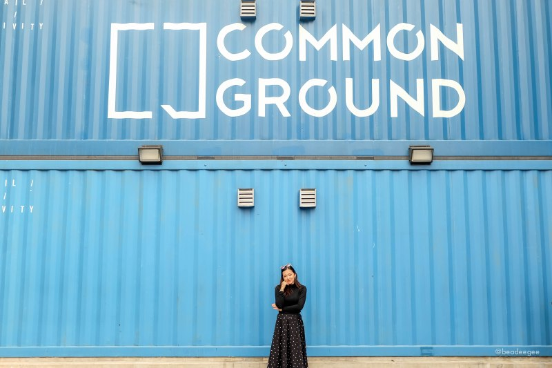 A girl in black in front of a blue artsy shipping container of Common Ground Seoul