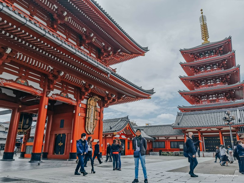 a man posing in front of entrance and pagoda in sensoji temple