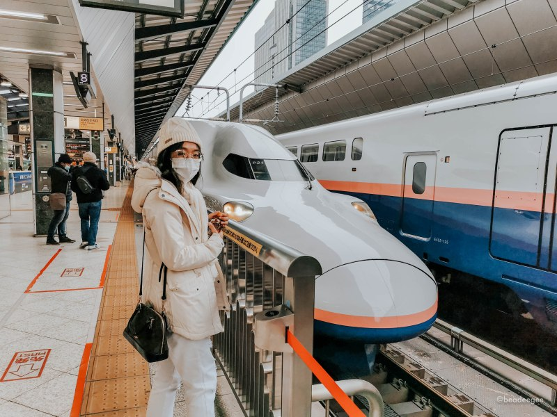 a girl in front of a bullet train in tokyo station