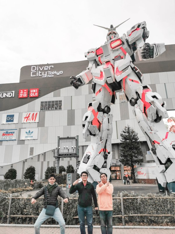 3 boys in front of real size gundam in odaiba