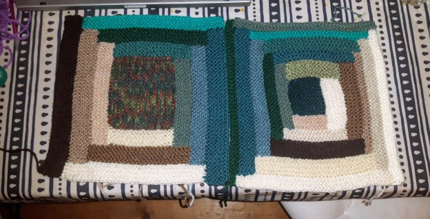 two scrappy green brown a cream coloured knitted log cabin blocks sit on a blue and white table cloth.