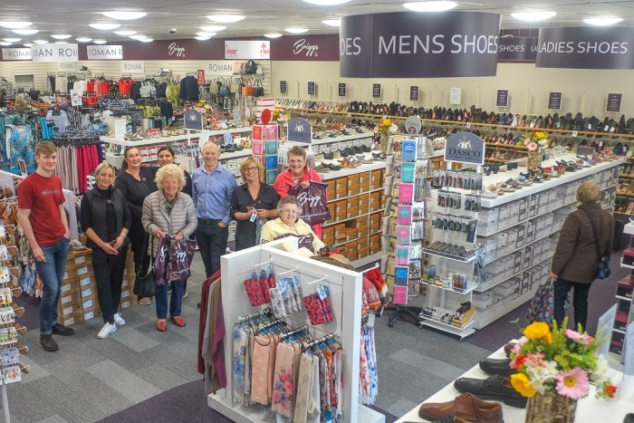 image of Briggs shoes owner Tom Powney and staff and customers in the Briggs Shoes shop.