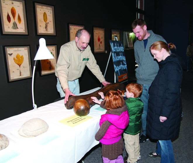 Visitors to Paleopalooza enjoy touching a real fossil with the help of Academy Vertebrate Paleontology Collection Manager Ned Gilmore. Credit: Will Klein