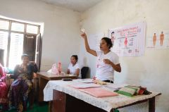 4 Oligaun Yamkala explaining what what the menstrual cup is to the group of women and girls not in the school