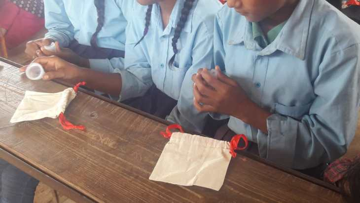 Girls with our Ruby Cup menstrual cups in a menstrual education workshop