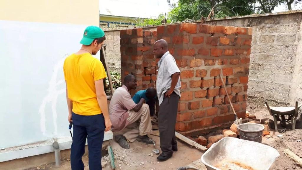 Construction derrière le bâtiment d\'un petit local pour le compresseur.