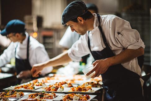 A chef adding garnishes to dishes at Ristorante Beatrice.