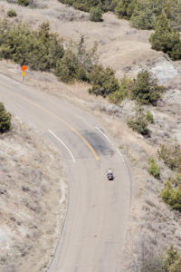 A motorcycle passes below on the road in the Theodore Roosevelt National Park.