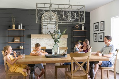 Family in their new dining room remodel | Black Shiplap walls with iron lighting fixture