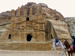 Two men and three horses race past the Obelisk Tomb and the Triclinium in Petra - by Anika Mikkelson - Miss Maps - www.MissMaps.com
