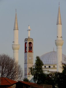Ebu Beker Mosque Minaretes with Catholic Church Bell Tower in Background - near center - Shkoder Albania - by Anika Mikkelson - Miss Maps - www.MissMaps.com