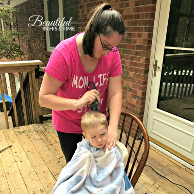 mom giving toddler a haircut