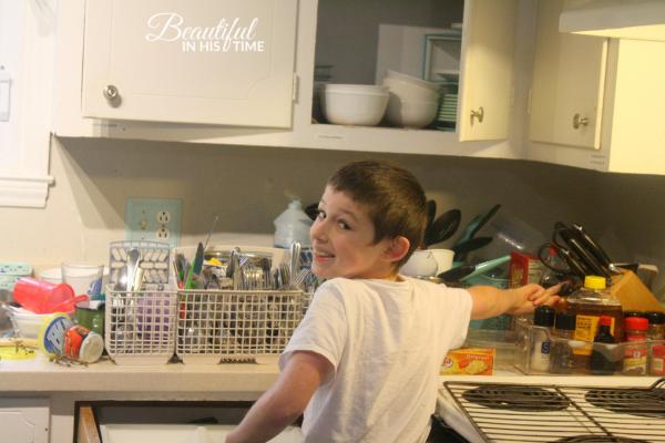 boy unloads dishwasher