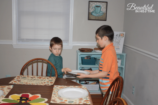 two boys set the table for Thanksgiving dinner