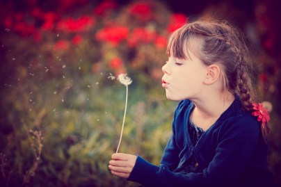 Girl blowing on dandelion seeds