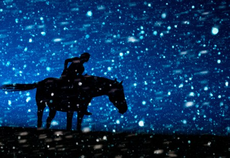 Woman and horse silhouetted against the blue night winter sky in a winter snowstorm