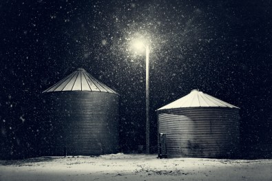 Grain bins protecting summer's wheat harvest from the cold and snow on a winter night.