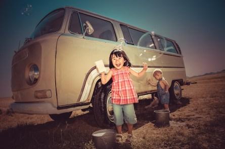 Happy children washing vintage VW van