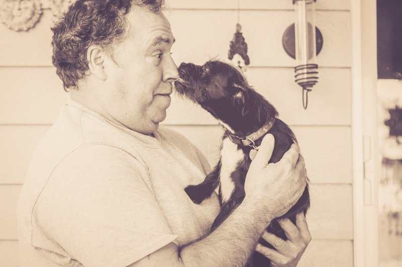 Sweet little dog stealing a slobbery kiss from his man