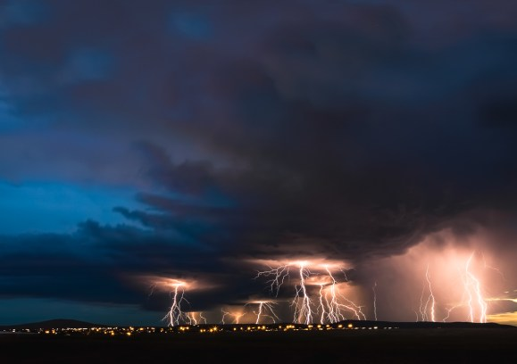 Lightning striking beyond hills on the horizon. Tri-Cities, WA