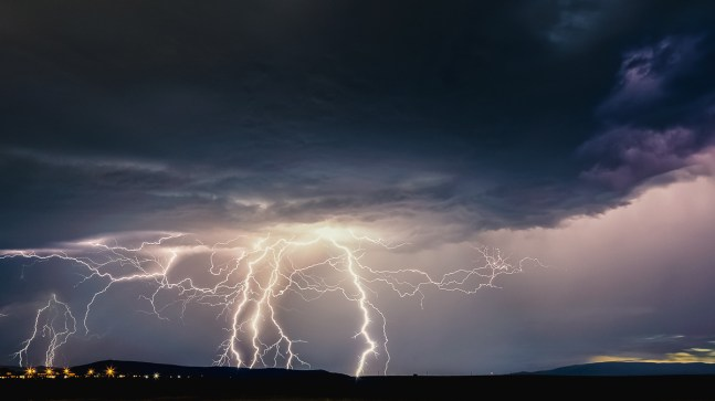 Lightning striking beyond hills on the horizon. Tri-Cities, WA