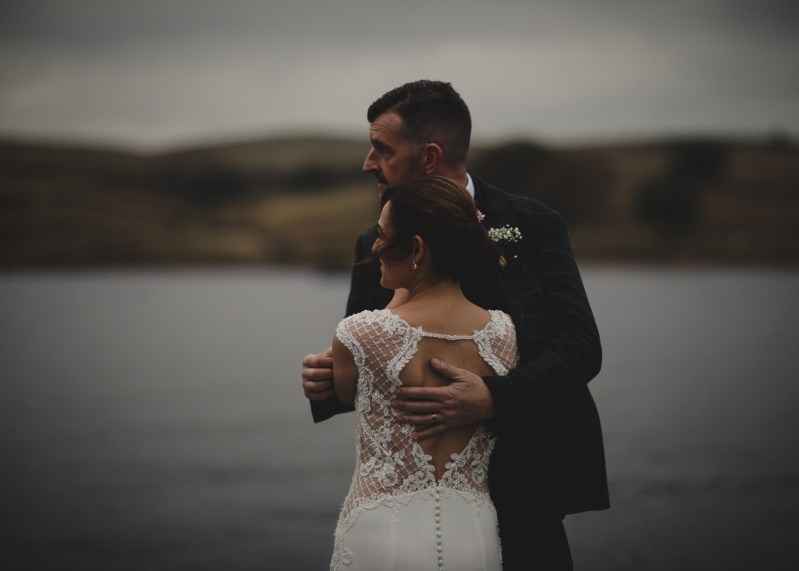 Groom holds his bride by the waterside at Kielder