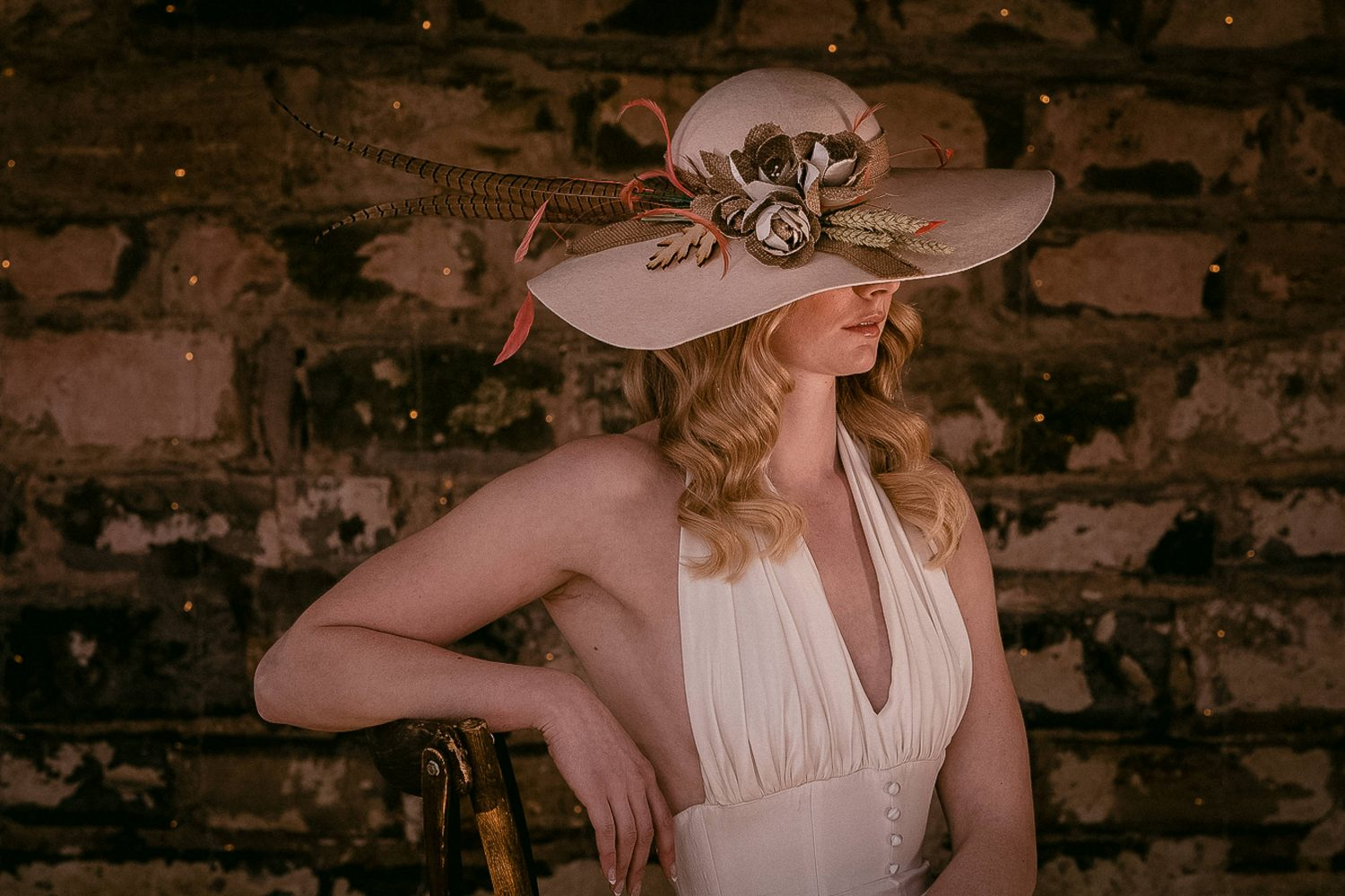 Portrait of a boho styled bride wearing a wide brimmed hat