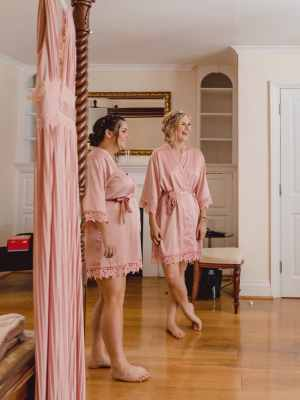Bridesmaids in pink robes waiting to get ready
