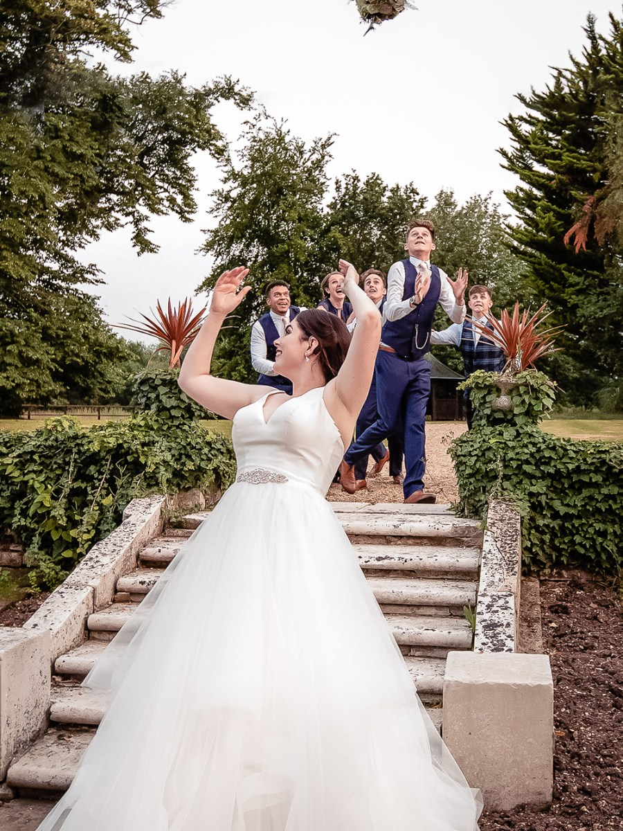 Bride throuwing her bouquet over her head. Donny & Olivia at Silchester House