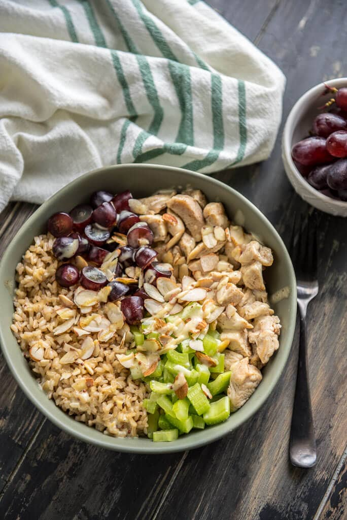 A bowl of healthy chicken salad brown rice bowl with grapes and celery with a napkin and a fork and bowl of grapes