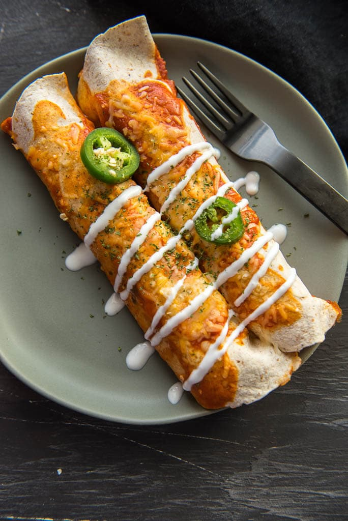 Overhead photo of two vegetarian enchiladas with drizzle and jalapeños