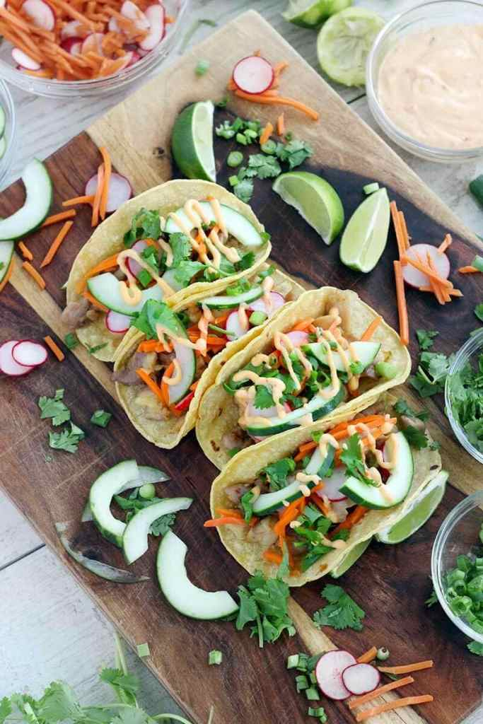 Overhead view of Banh Mi Tacos on a wooden platter with veggies and limes