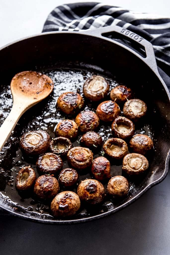 Cast iron skillet with sautéed mushrooms and a wooden spoon and napkin