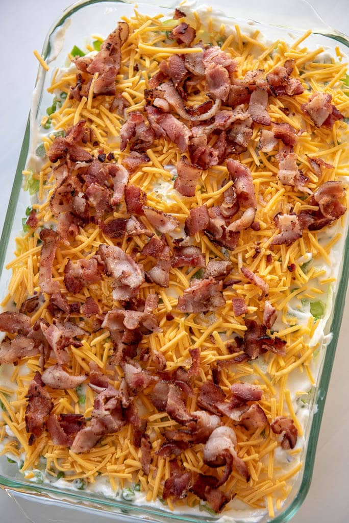 Overhead view of 7 layer salad with cheese and bacon on top