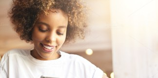 black girl smiling with a phone