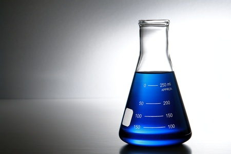 10487906 - laboratory glass erlenmeyer conical flask filled with blue chemical liquid for a chemistry experiment in a science research lab