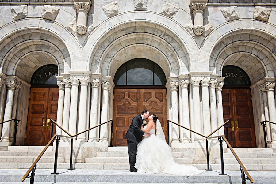 Bride and Groom Kissing on Steps of Sacred Heart Catholic Church in Downtown Tampa