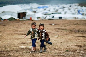 Syrian boys , whose family fled their home in Idlib, walk to their tent, at a camp for displaced Syrians. https://www.flickr.com/photos/syriafreedom/8309708775