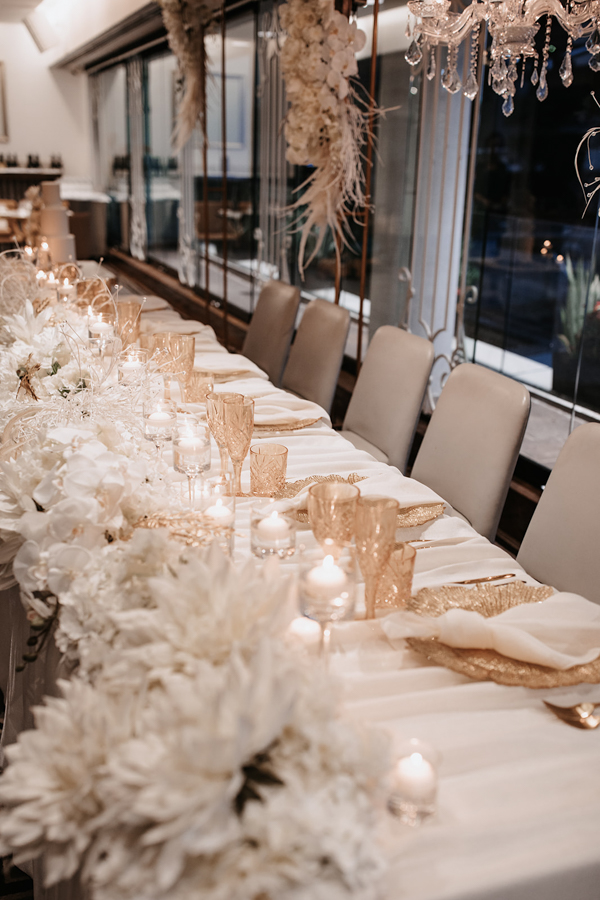 blackbird-wedding-reception-styling-amber-crystal-stemware-faux-flower-floral-ivory-linen-napkins-gold-charger-plates-cutlery-chandelier