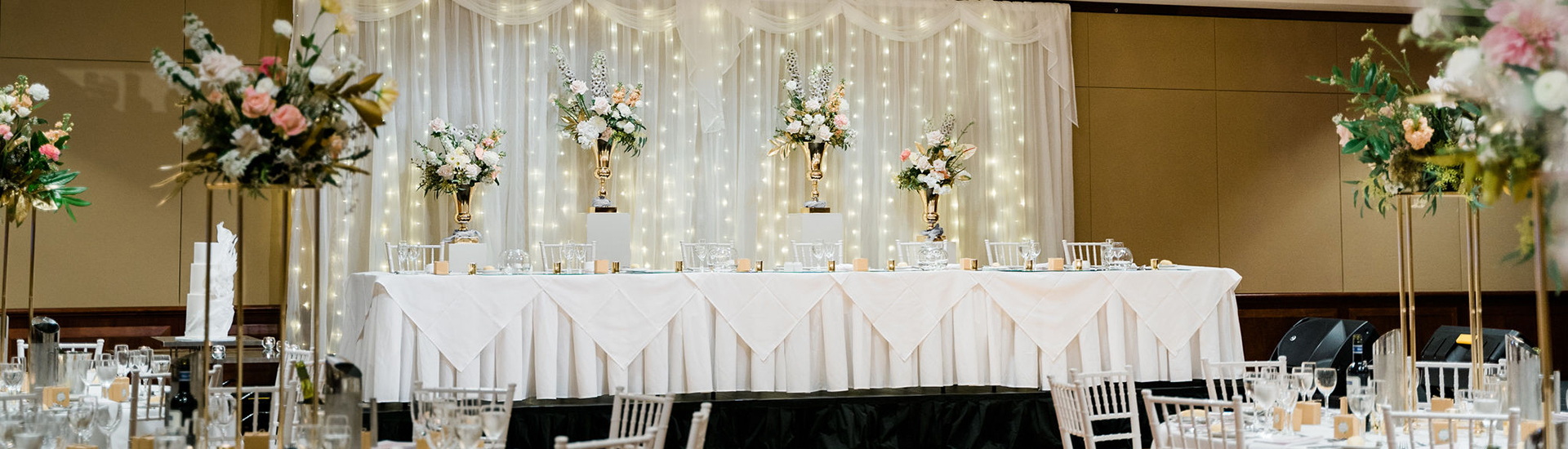 Samantha-&-Jordan-royal-on-the-park-hotel-wedding-reception-gold-stand-fresh-flower-floral-centrepiece-bridal-table-fairylight-backdrop-white-pedestal-plinth-gold-urn-banner