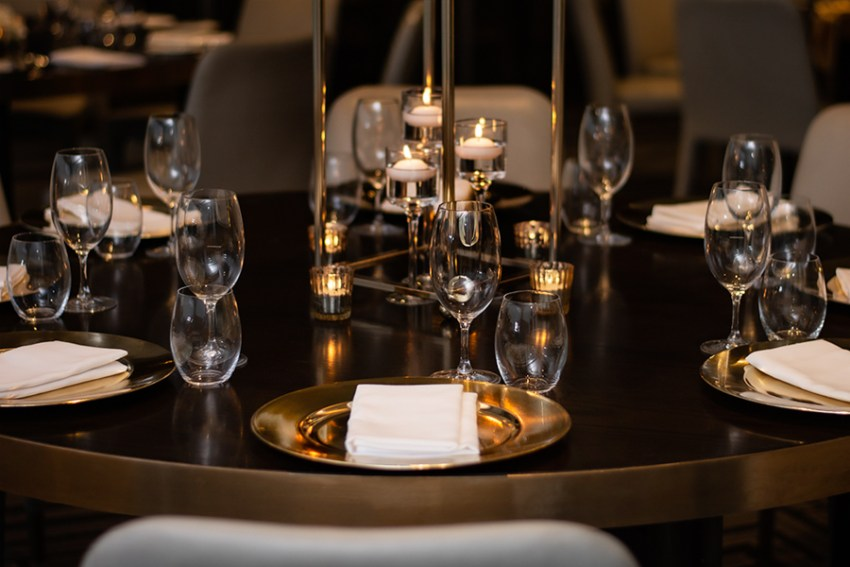 blackbird-wedding-reception-styling-gold-stand-table-centrepiece-floating-candles-gold-charger-plate