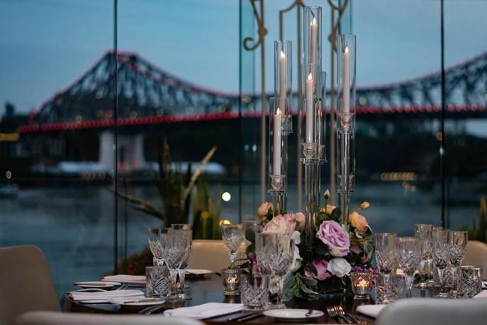 blackbird-wedding-reception-styling-glass-candelabra-candlestick-holder-guest-table-centrepiece-faux-silk-flower-florals-brisbane-storey-bridge-view
