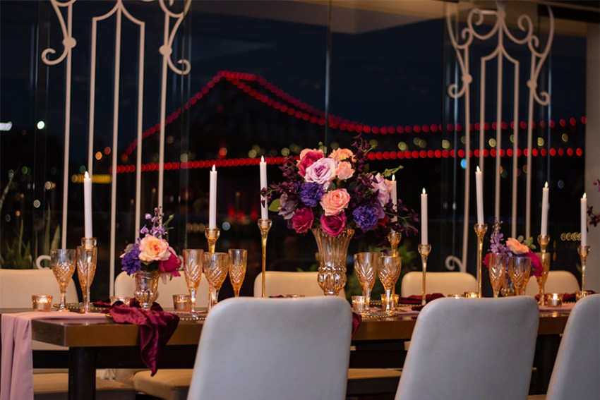 blackbird-wedding-reception-styling-amber-crystal-stemware-candlestick-holders-bright-faux-silk-flower-floral-arrangement-burbundy-velvet-napkins-gold-beaded-glass-charger-plates-brisbane-storey-bridge-view