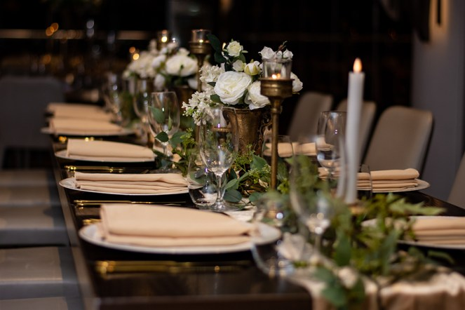 blackbird-wedding-reception-styling-brushed-gold-candle-holders-faux-silk-greenery-floral-linen-napkins-rustic-charger-plates