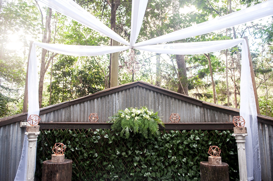walkabout-creek-wedding-ceremony-rainforest-white-draping-greenery-copper-hex-geo-lanterns-log-column-pedestal