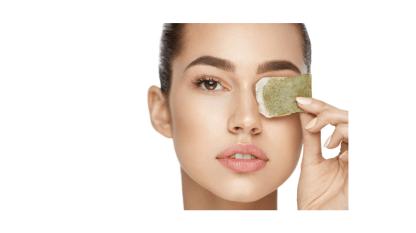 Eine Frau mit natürlichem Make-up legt sich einen Teebeutel auf ihr Auge.